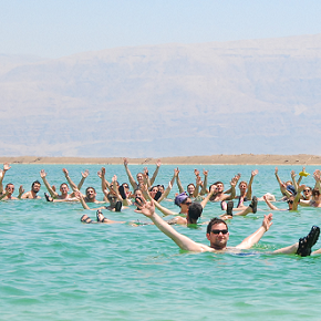 People floating in the Dead Sea with their arms up